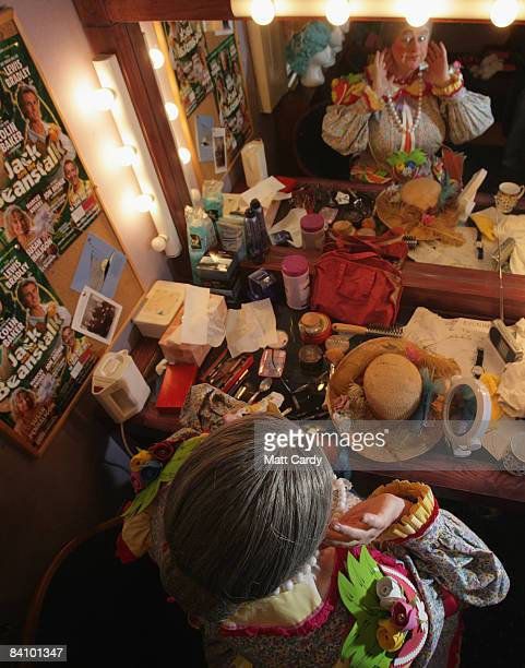 Chris Harris applies the finishing touches to his makeup in his dressing room backstage as he prepares for his role as Dame Trott in the production...