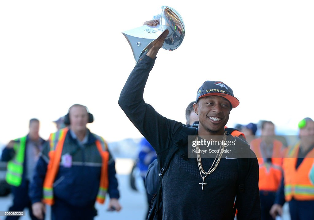 Chris Harris holds up the Vince Lombardi Trophy as members of the Denver Broncos football team arrive home at Denver international Airport on Monday, Feb. 8, 2016.