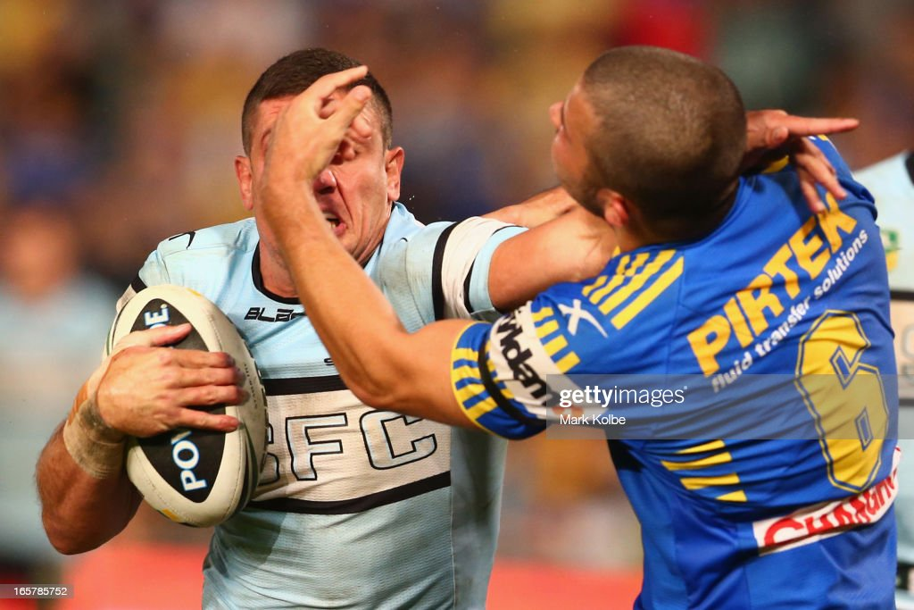 Chris Heighington of the Sharks is tackled by Luke Kelly of the Eels during the round five NRL match between the Parramatta Eels and the Cronulla Sharks at Parramatta Stadium on April 6, 2013 in Sydney, Australia.