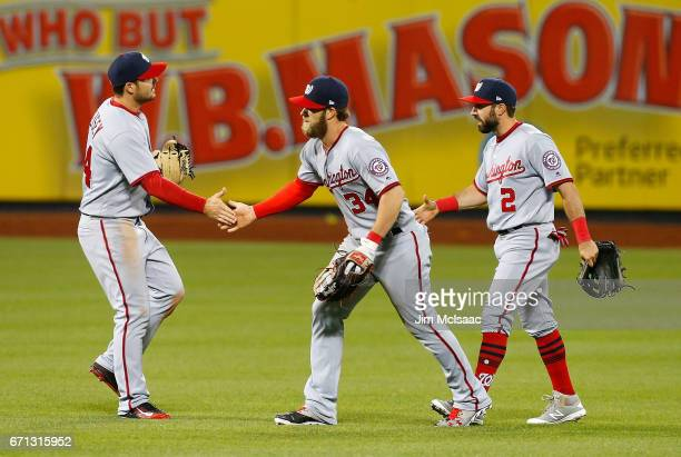 Chris Heisey Bryce Harper and Adam Eaton of the Washington Nationals celebrate after defeating the New York Mets in eleventh inning at Citi Field on...