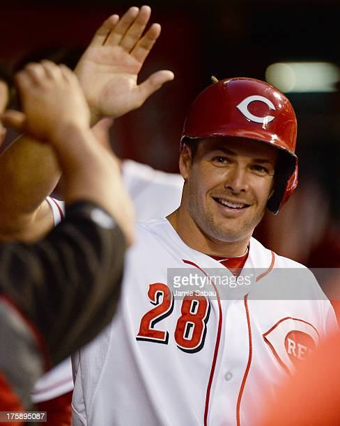 Chris Heisey of the Cincinnati Reds celebrates in the dugout after scoring in the fifth inning against the San Diego Padres at Great American Ball...
