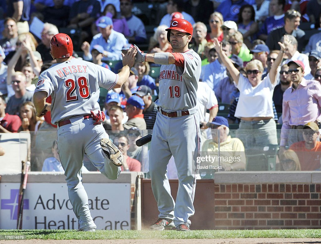 <a gi-track='captionPersonalityLinkClicked' href=/galleries/search?phrase=Chris+Heisey&family=editorial&specificpeople=5971787 ng-click='$event.stopPropagation()'>Chris Heisey</a> #28 of the Cincinnati Reds is greeted by <a gi-track='captionPersonalityLinkClicked' href=/galleries/search?phrase=Joey+Votto&family=editorial&specificpeople=759319 ng-click='$event.stopPropagation()'>Joey Votto</a> #19 after scoring against the Chicago Cubs during the eighth inning on August 14, 2013 at Wrigley Field in Chicago, Illinois.