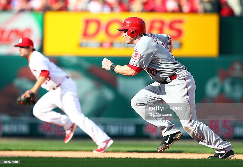 Chris Heisey #28 of the Cincinnati Reds leaves first base against the St. Louis Cardinals during Opening Day on April 8, 2013 at Busch Stadium in St. Louis, Missouri.