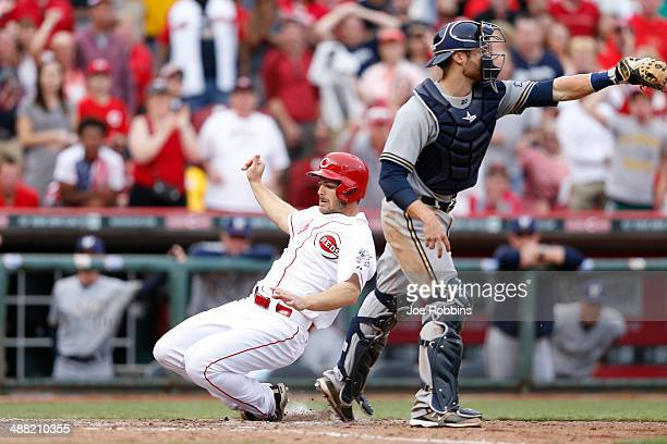 Chris Heisey of the Cincinnati Reds scores the winning run after a double by Todd Frazier in the tenth inning of the game against the Milwaukee...