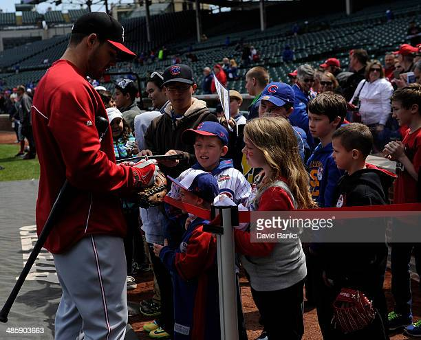 Chris Heisey of the Cincinnati Reds signs autographs on April 19 2014 at Wrigley Field in Chicago Illinois