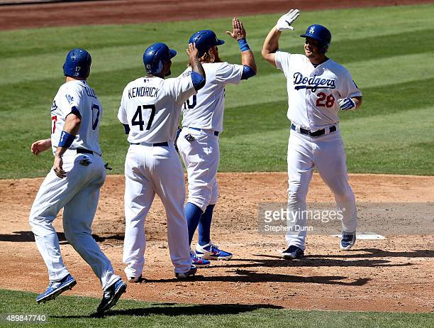 Chris Heisey of the Los Angeles Dodgers celebrates with Justin Turner Howie Kendrick and AJ Ellis as they all score on Heisey's grand slam home run...