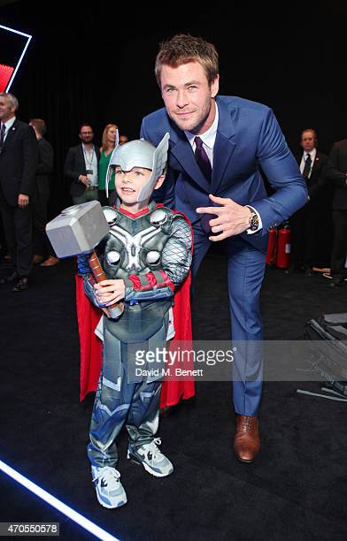 Chris Hemsworth poses with a young fan at the European premiere of 'The Avengers Age Of Ultron' at Westfield London on April 21 2015 in London England