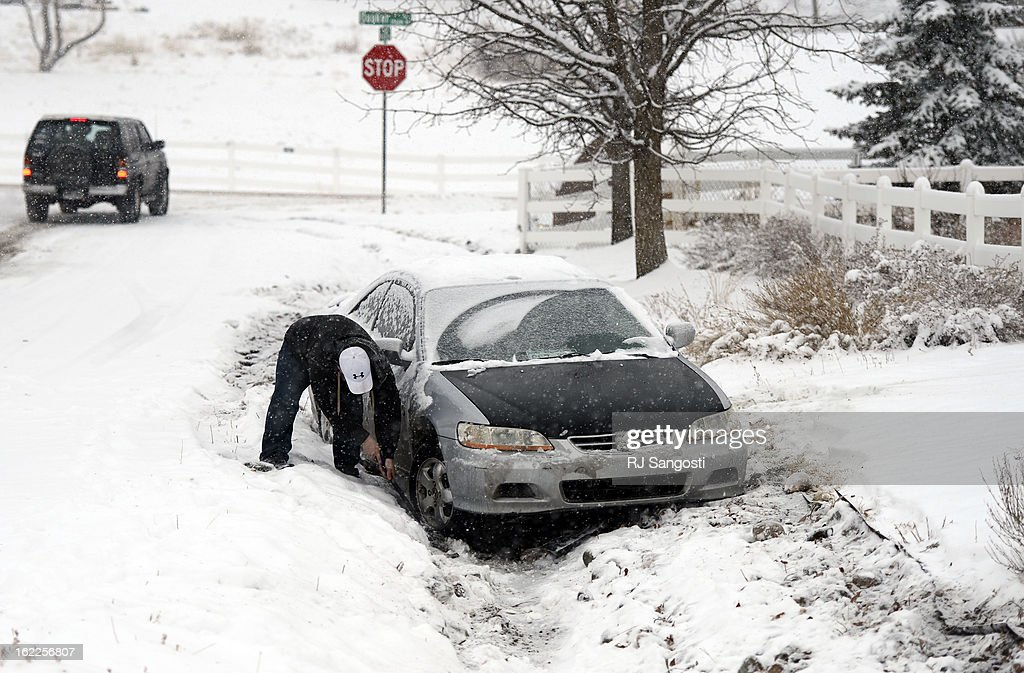 Chris Hendren tries to use his window scraper to dig out his car, February, 21, 2013, after sliding off the road into someones yard in west Arvada. The metro area was slowed by overnight snow, roads are snow packed, icy, and lane recognition is a problem along some stretches.