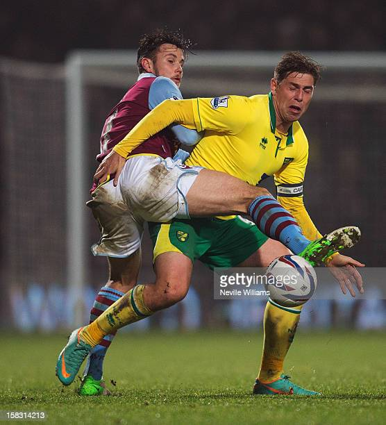 Chris Herd of Aston Villa challenges Grant Holt of Norwich City during the Capital One Cup Quarter Final match between Norwich City and Aston Villa...