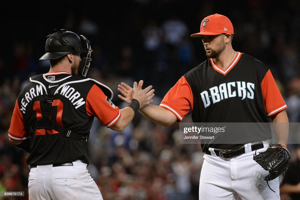 Chris Herrmann #10 and Jake Barrett #33 of the Arizona Diamondbacks wearing nickname-bearing jerseys celebrate after closing out the game against the San Francisco Giants at Chase Field on August 27, 2017 in Phoenix, Arizona.