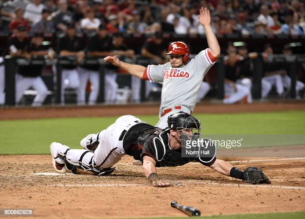 Chris Herrmann of the Arizona Diamondbacks stretches to catch a throw while keeping his toe on home plate to get a force out as Daniel Nava of the...