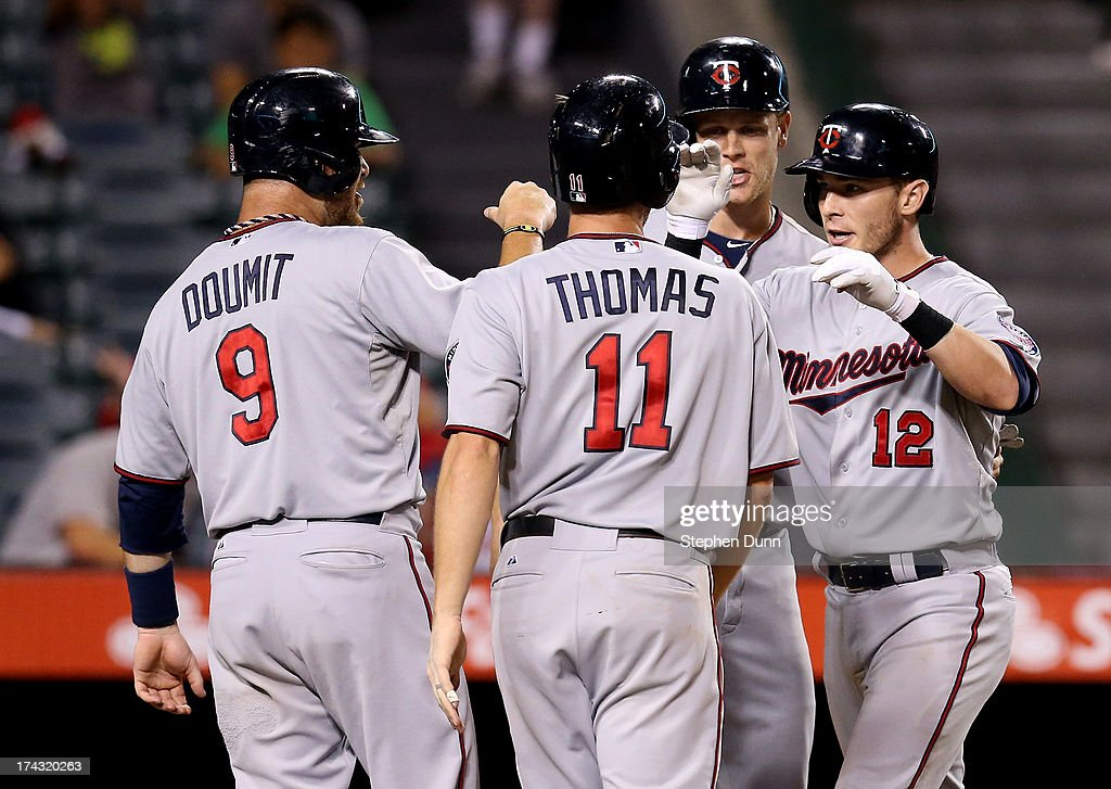 Chris Herrmann #12 of the Minnesota Twins celebrates with Justin Morneau #33, Clete Thomas #11, and Ryan Doumit #9 after they all score on Herrmann's grand slam home run in the 10th inning against the Los Angeles Angels of Anaheim at Angel Stadium of Anaheim on July 23, 2013 in Anaheim, California.
