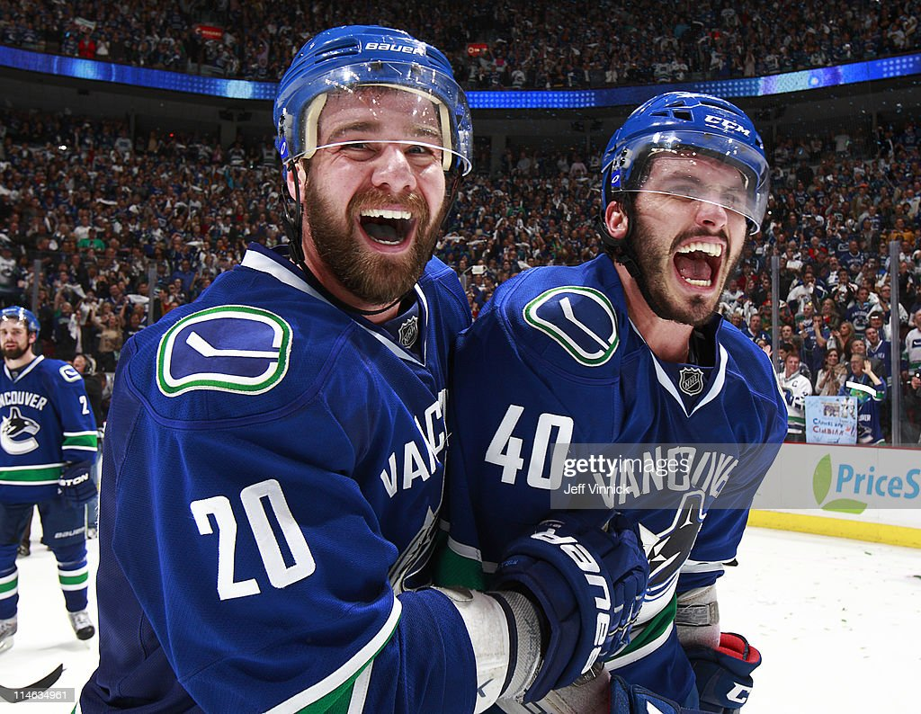 Chris Higgins and teammate Maxim Lapierre of the Vancouver Canucks celebrate their 32 overtime win over the San Jose Sharks in Game Five of the...