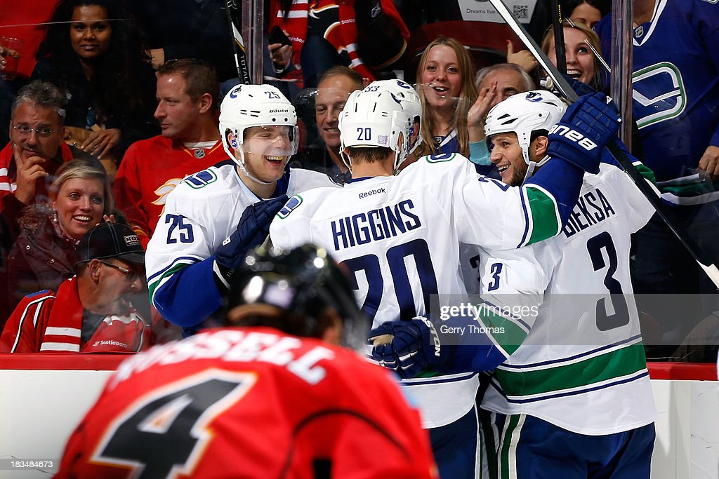 Chris Higgins #20, <a gi-track='captionPersonalityLinkClicked' href=/galleries/search?phrase=Kevin+Bieksa&family=editorial&specificpeople=688792 ng-click='$event.stopPropagation()'>Kevin Bieksa</a> #3 and teammates of the Vancouver Canucks celebrate a goal against the Calgary Flames at Scotiabank Saddledome on October 6, 2013 in Calgary, Alberta, Canada.