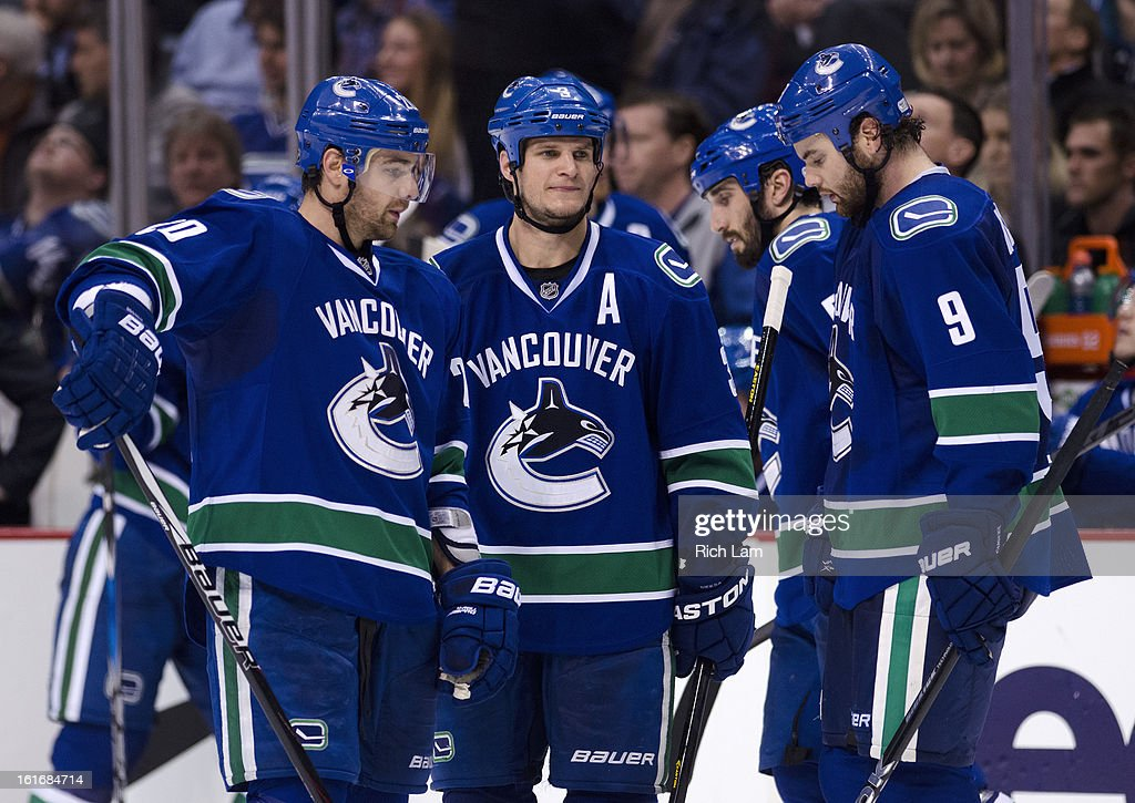 Chris Higgins #20, Kevin Bieksa #3 and Zack Kassian #9 of the Vancouver Canucks talk thing over during a break in NHL action against the Minnesota Wild as Jason Garrison #5 skates past in the background on February 12, 2013 at Rogers Arena in Vancouver, British Columbia, Canada.