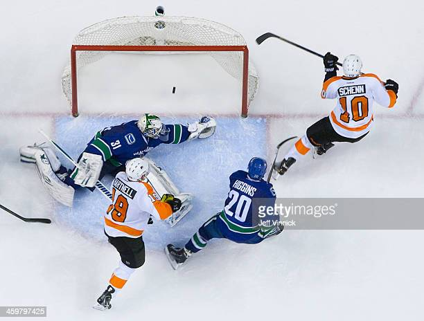 Chris Higgins of the Vancouver Canucks and Scott Hartnell of the Philadelphia Flyers looks on as Brayden Schenn of the Philadelphia Flyers scores on...
