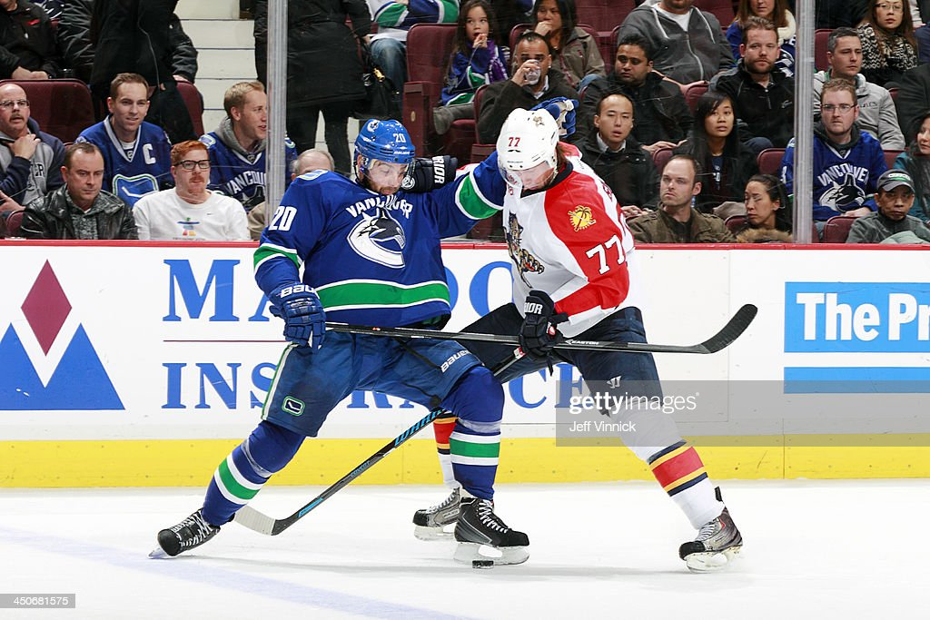 Chris Higgins #20 of the Vancouver Canucks and <a gi-track='captionPersonalityLinkClicked' href=/galleries/search?phrase=Tom+Gilbert&family=editorial&specificpeople=687083 ng-click='$event.stopPropagation()'>Tom Gilbert</a> #77 of the Florida Panthers battle for the puck during their NHL game at Rogers Arena on November 19, 2013 in Vancouver, British Columbia, Canada. Florida won 3-2 in a shootout.
