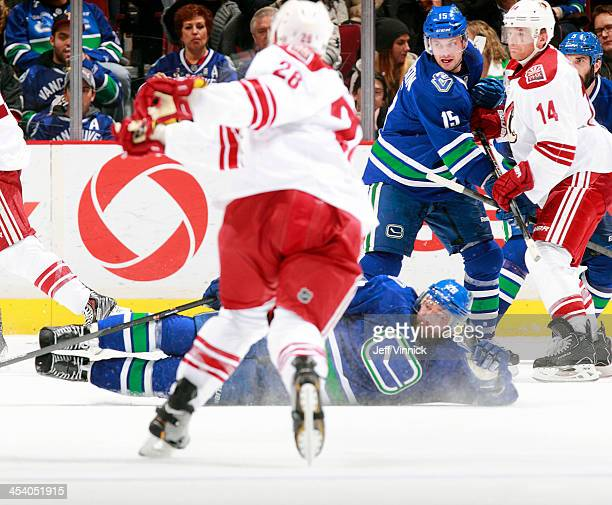 Chris Higgins of the Vancouver Canucks blocks a shot by Lauri Korpikoski of the Phoenix Coyotes while Brad Richardson of the Canucks ties up Jeff...