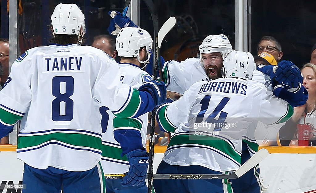 Chris Higgins #20 of the Vancouver Canucks celebrates his goal with Alex Burrows #14, Nick Bonino #13 against the Nashville Predators during an NHL game at Bridgestone Arena on March 31, 2015 in Nashville, Tennessee.