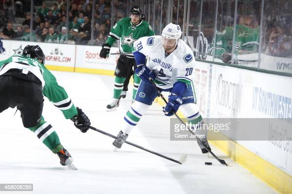 Chris Higgins of the Vancouver Canucks handles the puck against Sergei Gonchar of the Dallas Stars at the American Airlines Center on December 19...