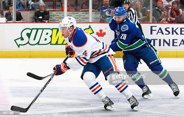 Chris Higgins of the Vancouver Canucks looks on as Taylor Hall of the Edmonton Oilers skates up ice with the puck during their NHL game at Rogers...