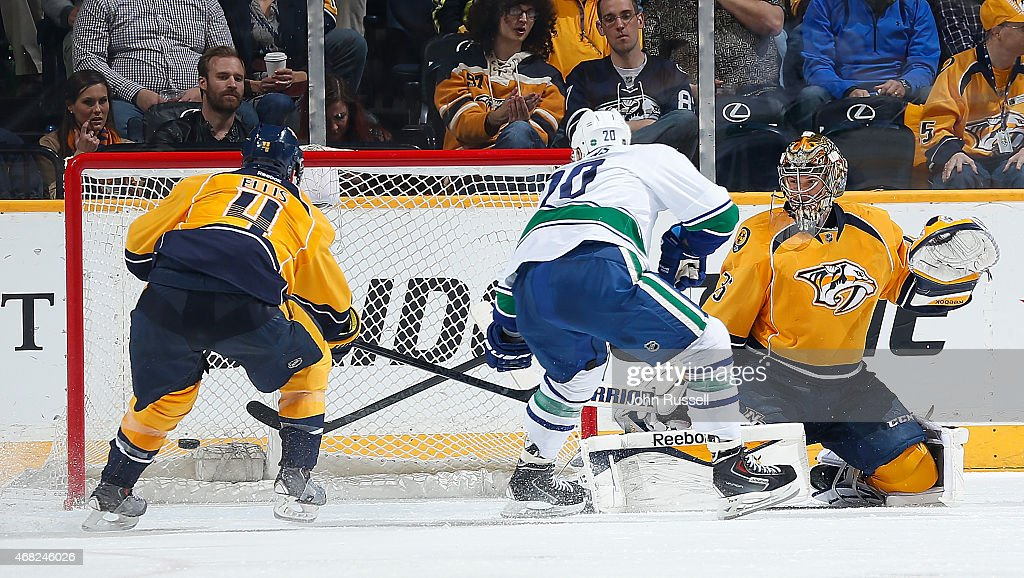 Chris Higgins #20 of the Vancouver Canucks puts the puck in the net against Pekka Rinne #35 of the Nashville Predators as Ryan Ellis #4 defends during an NHL game at Bridgestone Arena on March 31, 2015 in Nashville, Tennessee.