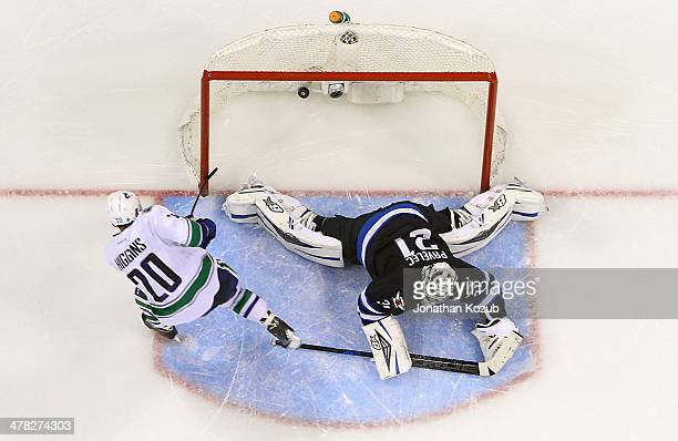 Chris Higgins of the Vancouver Canucks scores the shootout winner over a sprawling Ondrej Pavelec of the Winnipeg Jets at the MTS Centre on March 12...