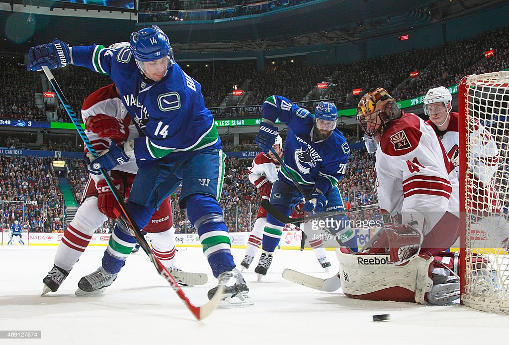 Chris Higgins #20 of the Vancouver Canucks watches Mike Smith #41 of the Phoenix Coyotes makes a save on Alexandre Burrows #14 of the Canucks during their NHL game at Rogers Arena April 9, 2015 in Vancouver, British Columbia, Canada. Vancouver won 5-0.