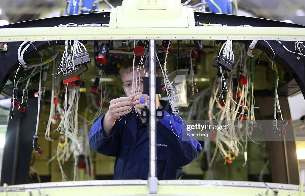 Chris Hodder, an apprentice at AgustaWestland, a unit of Finmeccanica SpA, works on wiring inside the cockpit of an AW159 helicopter, at the company's plant in Yeovil, U.K., on Thursday, June 12, 2014. U.K. unemployment declined more than expected and industrial production rose at the fastest annual pace since 2011, according to reports released this week. Photographer: Chris Ratcliffe/Bloomberg via Getty Images