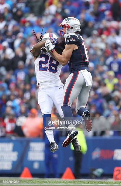 Chris Hogan of the New England Patriots comes down with the ball as Ronald Darby of the Buffalo Bills tries to make the strip during the first half...