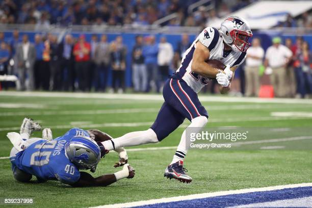 Chris Hogan of the New England Patriots scores a first quarter touchdown past the tackle of Jarrad Davis of the Detroit Lions during a preseason game...