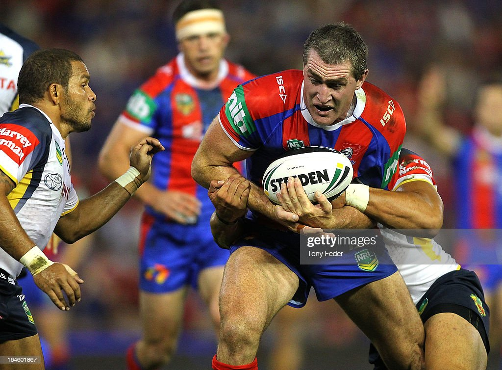 Chris Houston of the Knights passes through Cowboys defence during the round three NRL match between the Newcastle Knights and the North Queensland Cowboys at Hunter Stadium on March 25, 2013 in Newcastle, Australia.