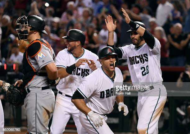 Chris Iannetta of the Arizona Diamondbacks celebrates with teammates JD Martinez and David Peralta after hitting a grand slam home run during the...
