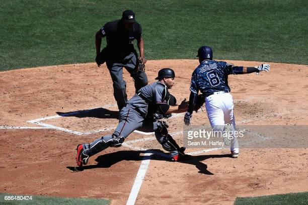 Chris Iannetta of the Arizona Diamondbacks tags out Erick Aybar of the San Diego Padres during the fifth inning of a game as umpire Ramon De Jesus...