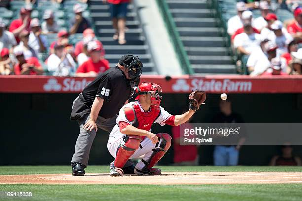 Chris Iannetta of the Los Angeles Angels of Anaheim catches as home plate umpire Wally Bell calls balls and strikes during the game against the...