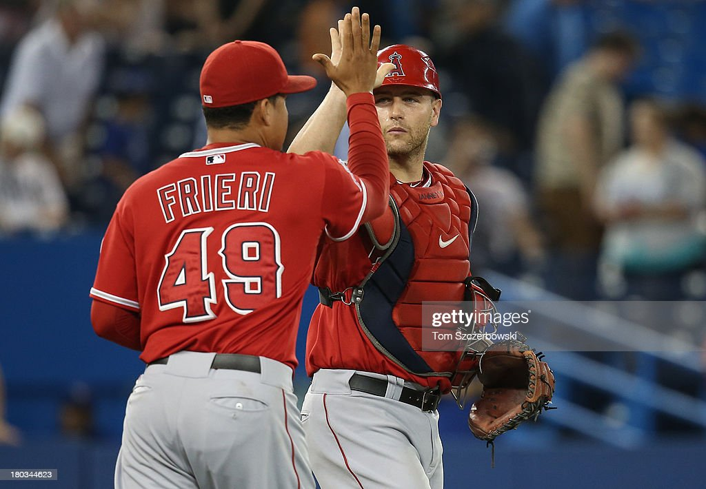 <a gi-track='captionPersonalityLinkClicked' href=/galleries/search?phrase=Chris+Iannetta&family=editorial&specificpeople=836137 ng-click='$event.stopPropagation()'>Chris Iannetta</a> #17 of the Los Angeles Angels of Anaheim celebrates their victory with <a gi-track='captionPersonalityLinkClicked' href=/galleries/search?phrase=Ernesto+Frieri&family=editorial&specificpeople=4947122 ng-click='$event.stopPropagation()'>Ernesto Frieri</a> #49 during MLB game action against the Toronto Blue Jays on September 11, 2013 at Rogers Centre in Toronto, Ontario, Canada.