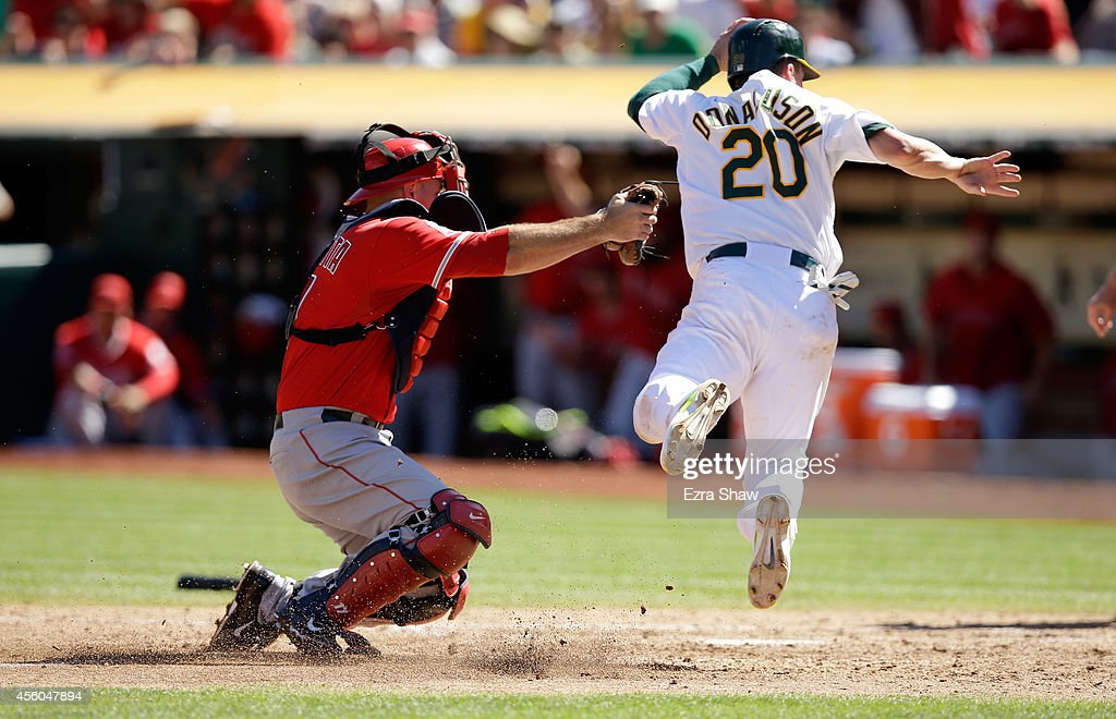 Chris Iannetta #17 of the Los Angeles Angels of Anaheim tags out a diving Josh Donaldson #20 of the Oakland Athletics in the fourth inning at O.co Coliseum on September 24, 2014 in Oakland, California. Manager Bob Melvin of the Oakland Athletics asked for a review of the play and the ruling on the field was confirmed.