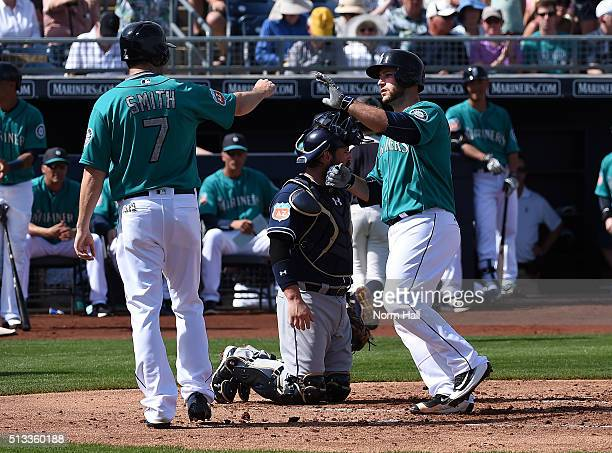 Chris Iannetta of the Seattle Mariners and teammate Seth Smith celebrate a second inning home run against the San Diego Padres at Peoria Stadium on...