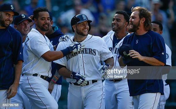 Chris Iannetta of the Seattle Mariners is congratulated by teammates after getting the gamewinning hit in the eleventh inning against the Tampa Bay...