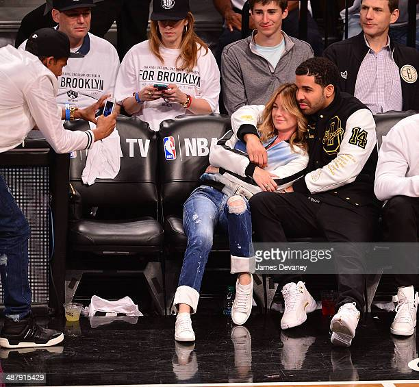 Chris Ivery Ellen Pompeo and Drake attend the Toronto Raptors vs Brooklyn Nets game at Barclays Center on May 2 2014 in the Brooklyn borough of New...