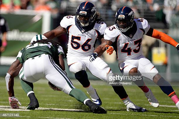Chris Ivory of the New York Jets is stopped for no gain by Nate Irving of the Denver Broncos and TJ Ward during the first half of action at MetLife...