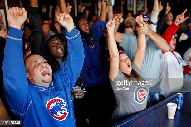 Chris Jacobson of Chicago and Chicago Cubs fans celebrate a three run home run by Javier Baez of the Chicago Cubs during the second inning of Game...