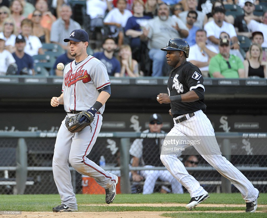 Chris Johnson #23 of the Atlanta Braves can't make a catch of a foul ball as Alejandro De Aza #30 of the Chicago White Sox runs nearby during the eighth inning on July 20, 2013 at U.S. Cellular Field in Chicago, Illinois. The Chicago White Sox defeated the Atlanta Braves 10-6.