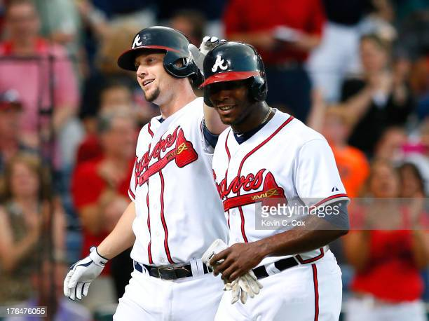 Chris Johnson of the Atlanta Braves celebrates his tworun homer against the Philadelphia Phillies in the third inning with Justin Upton at Turner...