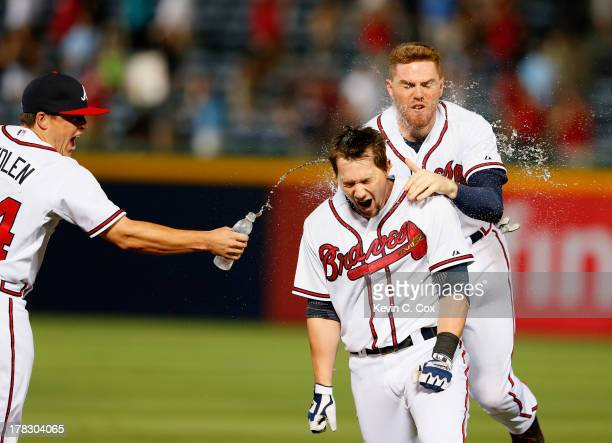 Chris Johnson of the Atlanta Braves celebrates with Freddie Freeman and Kris Medlen after hitting a walkoff RBI single in the ninth inning against...