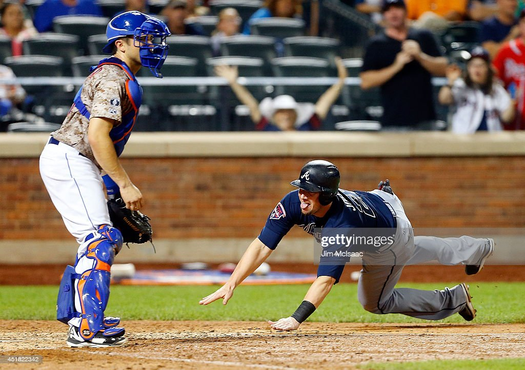 Chris Johnson #23 of the Atlanta Braves dives at home plate for an eighth-inning run against Travis d'Arnaud #15 of the New York Mets at Citi Field on July 7, 2014 in the Flushing neighborhood of the Queens borough of New York City.