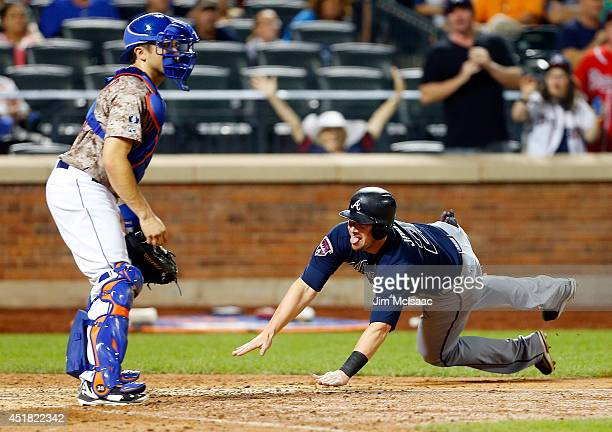 Chris Johnson of the Atlanta Braves dives at home plate for an eighthinning run against Travis d'Arnaud of the New York Mets at Citi Field on July 7...