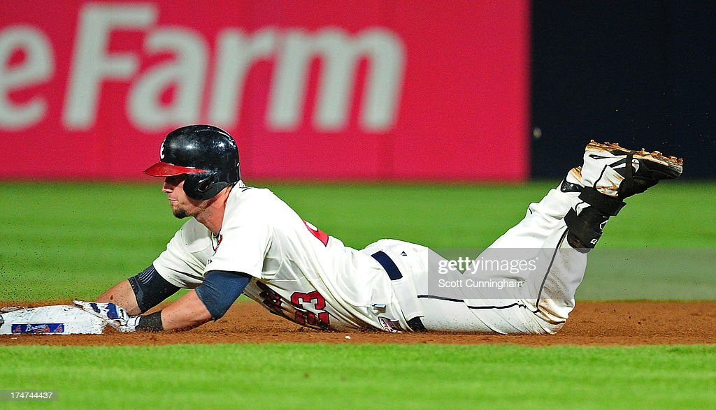 Chris Johnson #23 of the Atlanta Braves dives in to second base for a double against the St. Louis Cardinals at Turner Field on July 28, 2013 in Atlanta, Georgia.