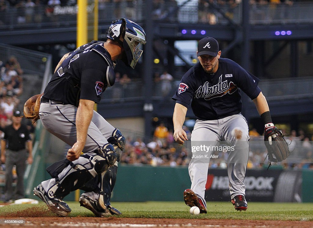 Chris Johnson #23 of the Atlanta Braves (right) fields a bunt in the third inning against the Pittsburgh Pirates during the game at PNC Park on August 19, 2014 in Pittsburgh, Pennsylvania.
