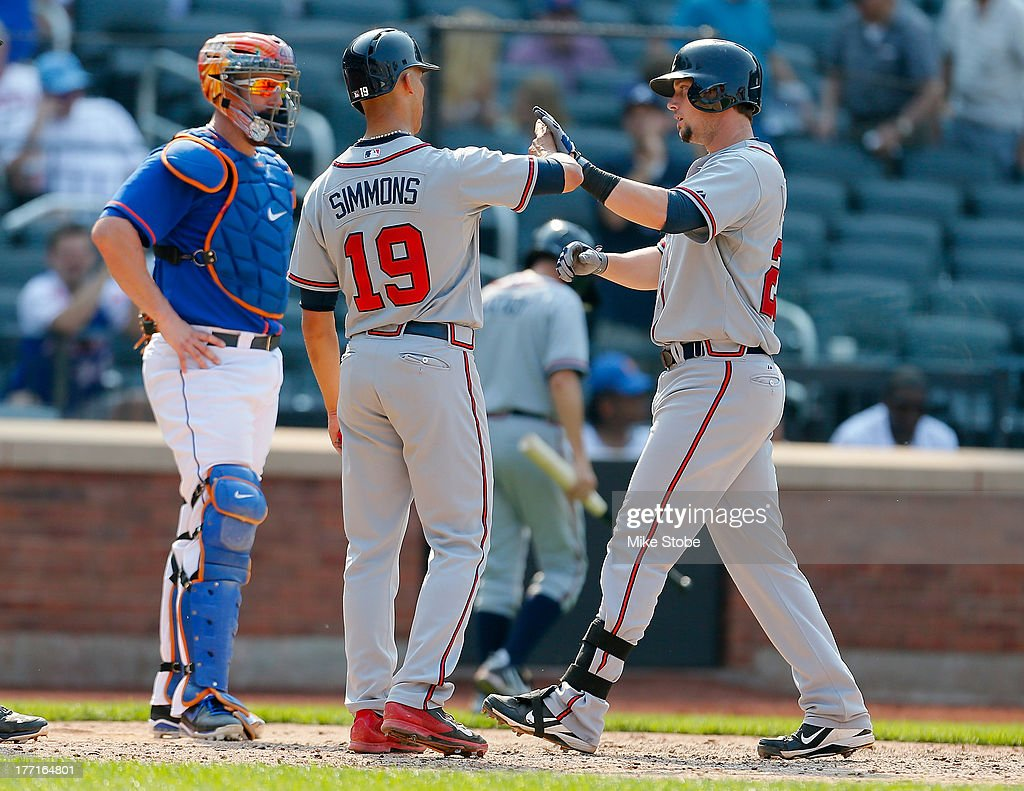 Chris Johnson #23 of the Atlanta Braves is greeted by <a gi-track='captionPersonalityLinkClicked' href=/galleries/search?phrase=Andrelton+Simmons&family=editorial&specificpeople=8978424 ng-click='$event.stopPropagation()'>Andrelton Simmons</a> #19 after connecting on a three run home run in the tenth inning against the New York Mets at Citi Field on August 21, 2013 at Citi Field in the Flushing neighborhood of the Queens borough of New York City. Braves defeated the Mets 4-1.